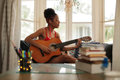 Mixed Race Girl Singing And Playing Classic Guitar At Home Royalty Free Stock Photo