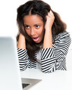 Mixed race teen girl, shocked looking at laptop Royalty Free Stock Photo