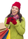 Mixed race woman holding shopping bags texting on cell phone wearing winter clothing isolated white background Royalty Free Stock Image