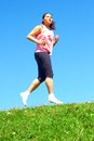 Mixed race woman jogging sporty color image copy space asian ethnicity female running with green grass and blue sky Stock Photo
