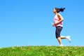 Mixed race woman jogging sporty color image copy space asian ethnicity female running with green grass and blue sky Royalty Free Stock Image