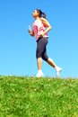 Mixed race woman jogging sporty color image copy space asian ethnicity female running with green grass and blue sky Royalty Free Stock Photos