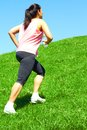 Mixed race woman jogging uphill sporty color image copy space asian ethnicity female running with green grass and blue sky Stock Photo