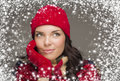 Mixed race woman wearing winter hat and gloves enjoys snowfall happy watching the snow fall looking to the side on gray background Royalty Free Stock Image