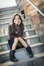 Mixed race young adult woman portrait on staircase of a pretty sitting a wearing leather boots and jacket Royalty Free Stock Photo