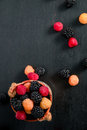 Mixed of red, black, yellow raspberries in a basket on black wooden background. Close up. Top view. Copy spase. Royalty Free Stock Photo