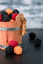 Mixed of red, black, yellow raspberries in a basket on  wooden background. Close up. Royalty Free Stock Photo