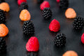 Mixed of red, black, yellow raspberries on  table. Close up. Royalty Free Stock Photo