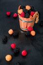 Mixed of red, black, yellow raspberries in a wooden basket and berry on black table. Close up. Royalty Free Stock Photo