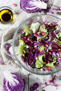 Mixed salad on bowl with red beans seeds and purple cabbage with separate seasoning white table Royalty Free Stock Photography
