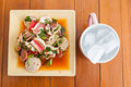 Mixed salad and a glass of water spicy placed on table made of wood Stock Image