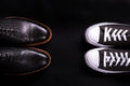 Mixed shoes. Oxford and sneakers shoe on black background. Different style of men fashion. Compare formal casual. Top view. Cop Royalty Free Stock Photo