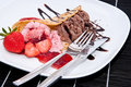 Mixed strawberry and chocolate ice cream on a plate against black background Royalty Free Stock Photography