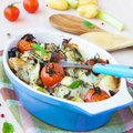 Mixed vegetable in blue bowl baked in the oven with cheese vegetables potato zucchini eggplant tomato mozzarella delicious Royalty Free Stock Photo