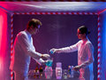 Mixing chemicals in a containment tent two scientists men and woman working with lit by gradient red and blue light Stock Photography