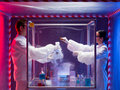 Mixing chemicals in a sealed enclosure two scientists men and woman sterile chamber holding glass container labeled as bio Stock Images