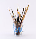 Mixture of different kinds and sizes of brushes on a white background in transparent cup Stock Images