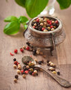Mixture of pepper peas in an old bowl and basil leaves Royalty Free Stock Photography