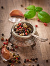 Mixture of pepper peas in an old bowl and basil leaves Royalty Free Stock Images