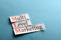 Mlm abbreviation multi level marketing on blue paper Stock Photography