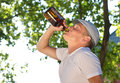 Mman drinking alcohol from a bottle in the park jobless depressed middle aged caucasian man Royalty Free Stock Photography