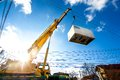 Mobile crane operating by lifting an electric generator and moving heavy Royalty Free Stock Photo