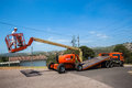 Mobile crane operator flat bed truck hoist machine controlled by from hydraulic extending arm off Stock Photography