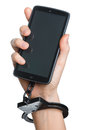 Mobile phone addiction concept. Smartphone and handcuff in hand Royalty Free Stock Photo
