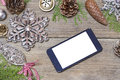 Mobile phone and the christmas decoration on a wooden background Royalty Free Stock Images