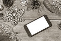Mobile phone and the christmas decoration on a wooden background toned image Royalty Free Stock Images