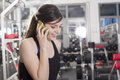 Mobile phone in gym sporty girl talking by the Royalty Free Stock Photos