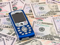 Mobile phone on money background Royalty Free Stock Photo