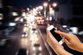 Mobile smart phone behind a blur of traffic. Royalty Free Stock Photo