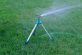 Mobile sprinkler system mounted on tripod working fresh green grass Stock Photo