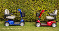 Mobility scooters a red and blue on the grass Stock Images