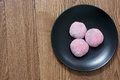 Mochi japanese sweet treat three balls pink rice with filling on the black plate Stock Image