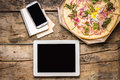Mock up freelancer workplace tablet pc cell phone and pizza top view image fast pizza delivery Royalty Free Stock Images