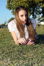 Mocking teen beautiful woman in the park grass Royalty Free Stock Images