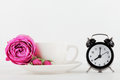 Mockup of coffee cup with rose flower and alarm clock on white desk with clean space for text and design your blogging. Royalty Free Stock Photo