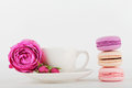 Mockup of coffee cup with rose flower and stack of macaroon on white table with empty space for text and design your blogging. Royalty Free Stock Photo