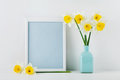 Mockup of picture frame decorated daffodil flowers in vase with clean space for text your blogging and greeting for mother day. Royalty Free Stock Photo