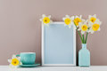 Mockup of picture frame decorated narcissus flowers in vase and coffee cup with clean space for text your blogging. Royalty Free Stock Photo