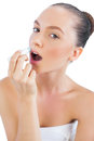 Model applying chap stick to lips Royalty Free Stock Photo