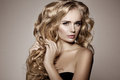 Model with blonde long hair. Waves Curls Hairstyle. Hair Salon. Royalty Free Stock Photo