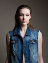 Model in blue denim jeans jacket close up portrait of a beautiful female fashion posing on gray background Stock Photography