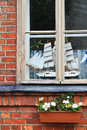 A model of boat in a window an old brick house Stock Photo