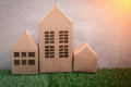 Model of cardboard house on green grass floor and grey backgroun Royalty Free Stock Photo