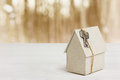Model of cardboard house with key against bokeh background. house building, loan, real estate or buying a new home