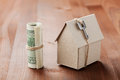 Model of cardboard house with key and dollar bills. House building, loan, real estate, cost of housing or buying a new home concep