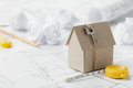 Model cardboard house with key and tape measure on blueprint. Home building, architectural and construction design concept Royalty Free Stock Photo